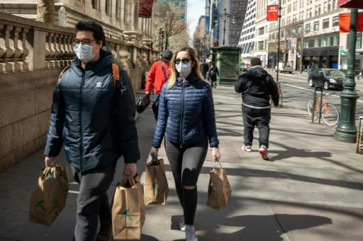 People carry groceries in New York City while wearing face masks and gloves on March 14