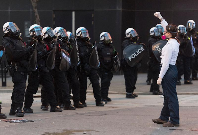 """A protester confronts a line of police officers during a demonstration calling for justice in the death of George Floyd and victims of police brutality, <a href=""""https://www.huffingtonpost.ca/entry/montreal-police-protest-black-racism_ca_5ed4722ac5b6d98601293616"""">in Montreal</a> on May 31, 2020."""