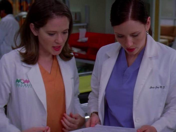April and Lexie in scrubs and white coats looking over a document together on greys anatomy