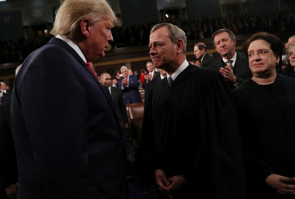 Donald Trump talks to Chief Justice John Roberts while Justice Elena Kagan looks on, in February last year.