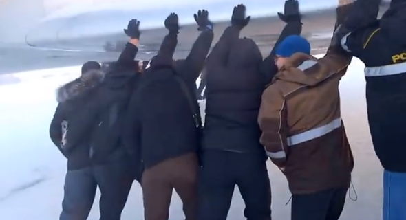 Plane passengers get out and push after landing gear freezes