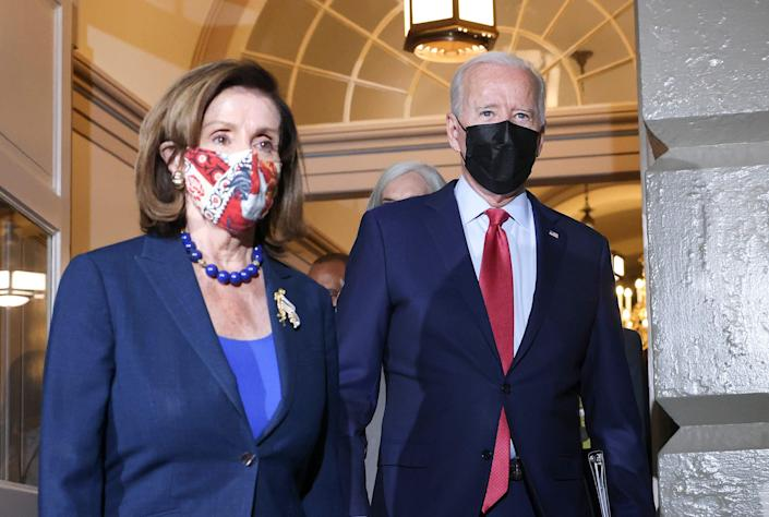 President Joe Biden walks with House Speaker Nancy Pelosi, D-Calif., as he arrives to meet with House Democrats at the U.S. Capitol on Oct. 1, 2021 in Washington, D.C. Biden called the meeting in order to push through an impasse with his infrastructure plan with $550 billion in new spending.