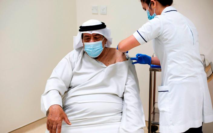 A health worker administering a dose of the coronavirus vaccine to a senior citizen at a medical center in the Dubai Emirate