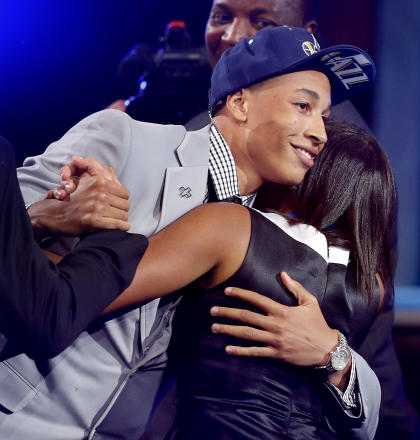 Dante Exum hugs friends and family after being selected. (AP)