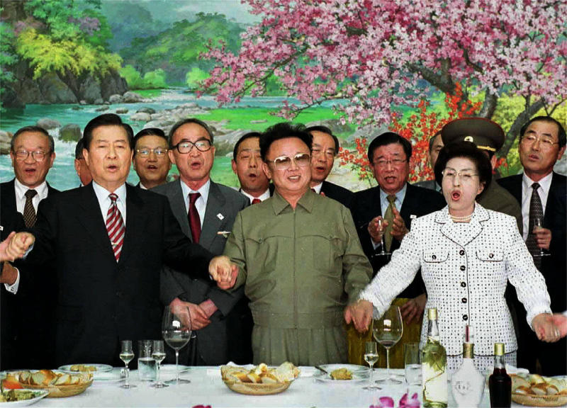 "FILE - In this June 15, 2000, file photo, from left in front row; former South Korean President Kim Dae-jung,  former North Korean leader Kim Jong Il, and former South Korean First Lady Lee Hee-ho, hold hands as they sing a song titled ""We Are Hoping For Reunification"" at the Baekhwawon Guest House in Pyongyang during a luncheon party Thursday, June 15, 2000. (AP Photo/KOREA POOL/YONHAP, File)"