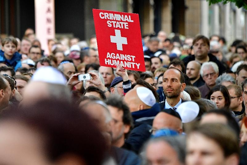 """A protester holds a placard during a """"Berlin wears kippa"""" demo in Berlin"""