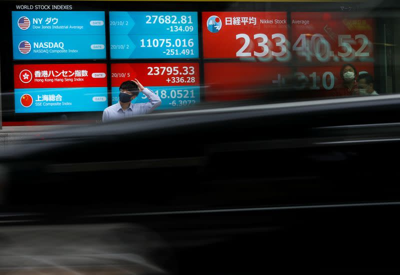 A passersby wearing a protective face mask stands in front of a screen displaying Nikkei share average and world stock indexes, amid the coronavirus disease (COVID-19) outbreak, in Tokyo