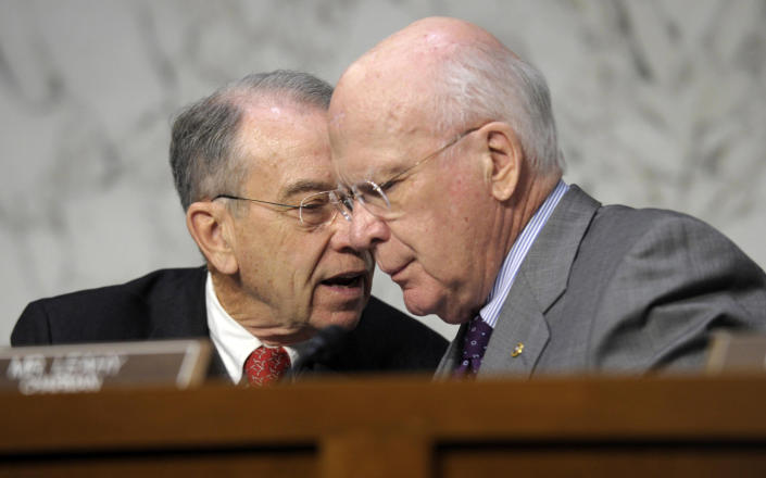 FILE – In this Feb. 13, 2013 file photo Senate Judiciary Committee Chairman Sen. Patrick Leahy, D-Vt., right, talks with the committee's ranking Republican Sen. Charles Grassley, R-Iowa on Capitol Hill in Washington. A divided Senate Judiciary Committee approved a Democratic bill Tuesday expanding required federal background checks to nearly all gun purchases, giving President Barack Obama an early victory on curbing gun violence in a fight that still faces difficult odds. The vote was 10-8, with all Democrats supporting the measure and every Republican opposing it. (AP Photo/Susan Walsh, File)
