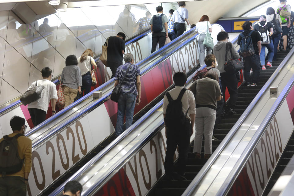 People ride escalators with banners to promote the Tokyo Olympics scheduled to open on July 23, in Tokyo, Tuesday, July 6, 2021. (AP Photo/Koji Sasahara)
