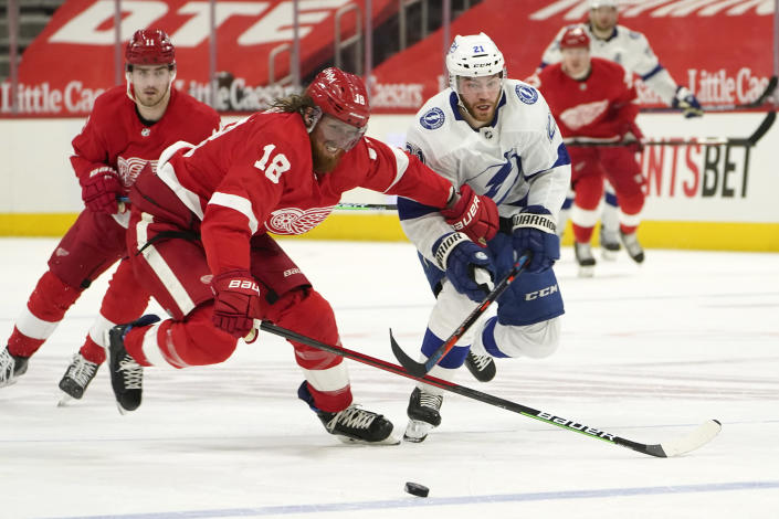 Detroit Red Wings defenseman Marc Staal (18) and Tampa Bay Lightning center Brayden Point (21) chase the puck in the first period of an NHL hockey game Saturday, May 1, 2021, in Detroit. (AP Photo/Paul Sancya)