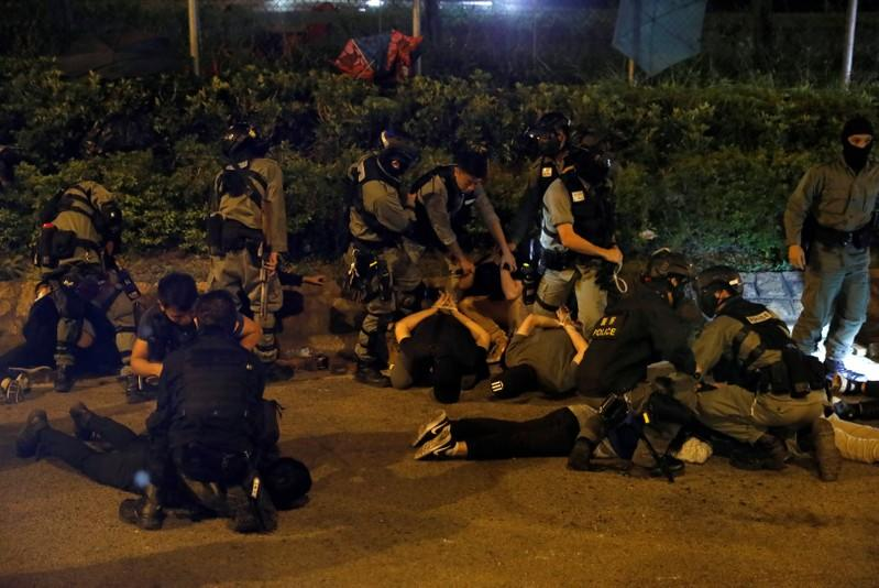 Detained protesters lay on the floor after they tried to leave Hong Kong Polytechnic University (PolyU) campus, in Hong Kong