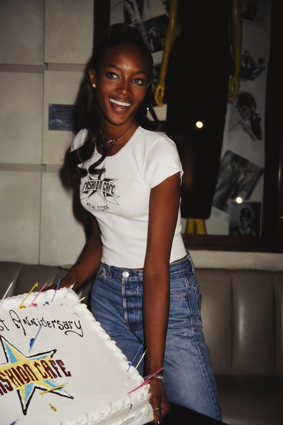 <p>Naomi Campbell embodies the 90s It girl with this simple white Tee and high-waisted jeans, 1996</p>