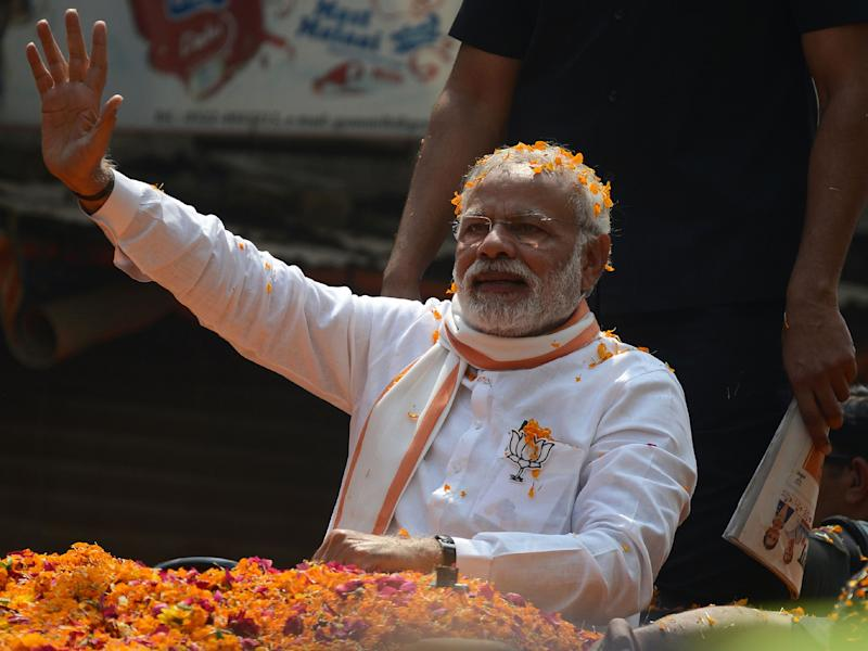 Indian Prime Minister Narendra Modi and Leader of the Bharatiya Janata Party (BJP) waves during a roadshow in support of state assembly election party candidates in Varanasi: AFP/Getty Images