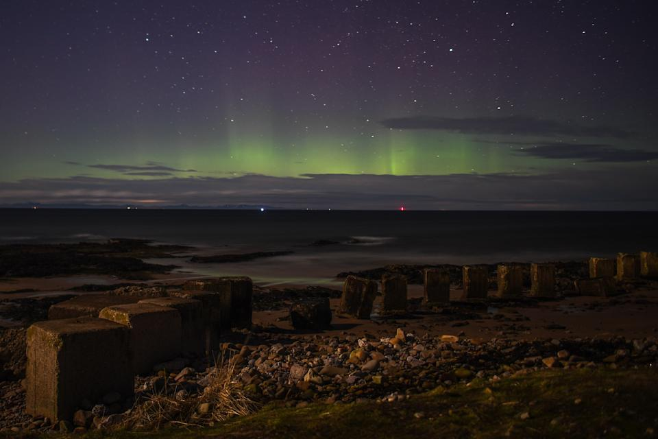 LOSSIEMOUTH, SCOTLAND - FEBRUARY 20: The Aurora Borealis is seen above WW2 beach defenses on February 20, 2021 in Lossiemouth, Scotland. The Aurora Borealis, more commonly known as the Northern Lights, occurs when solar winds drive charged particles from the sun which strike atoms and molecules in Earths atmosphere causing the light show. (Photo by Peter Summers/Getty Images)