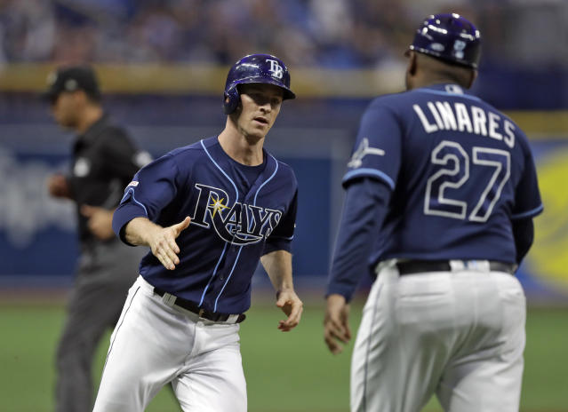 Tampa Bay Rays' Joey Wendle shakes hands with third base coach Rodney Linares (27) after his home run off New York Yankees starting pitcher Jonathan Loaisiga during the first inning of a baseball game Wednesday, Sept. 25, 2019, in St. Petersburg, Fla. (AP Photo/Chris O'Meara)