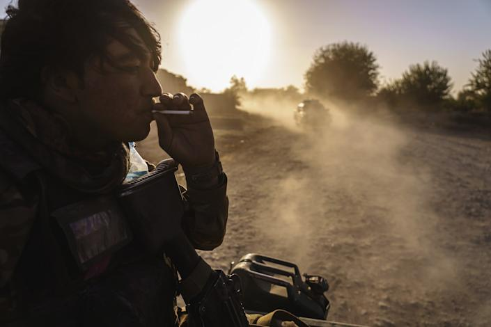 A man smokes in the back of a truck.
