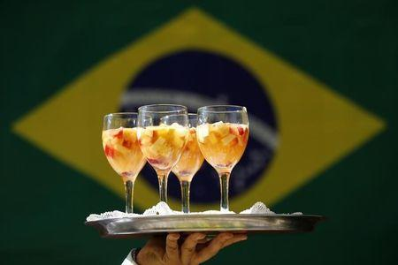 A waiter serves fruit cocktails as a group of friends watch Brazil play Chile in their round of 16 soccer match in a home in the upper class neighborhood of Lago Sul in Brasilia