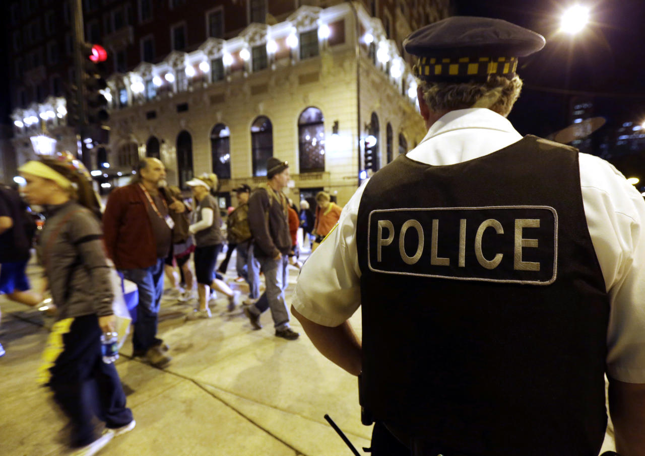 A Chicago Police officer looks around before start the Chicago Marathon in Chicago, Sunday, Oct. 13, 2013. The marathon is the first World Marathon Major in the United States since the Boston Marathon bombings last April and will be the most closely watched. (AP Photo/Nam Y. Huh)