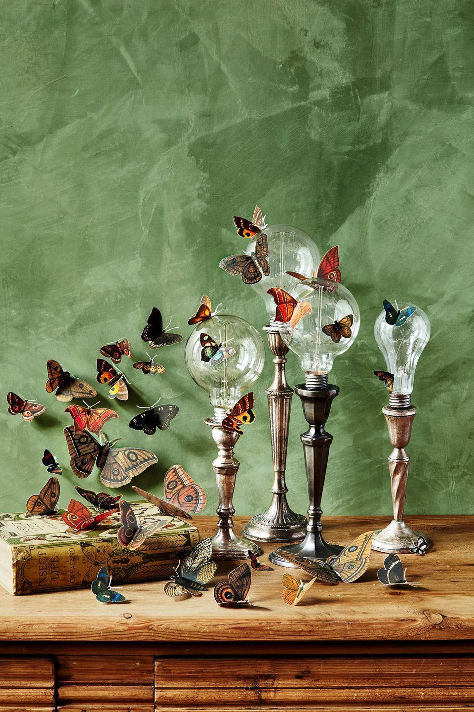 """<p>Affix clear lightbulbs on top of candlesticks (aged metal looks are a good choice) then add butterfly decals for a whimsical look. </p><p><a class=""""link rapid-noclick-resp"""" href=""""https://www.amazon.com/Butterfly-Stickers-Luminous-Removable-Butterflies/dp/B08221MVX2/?tag=syn-yahoo-20&ascsubtag=%5Bartid%7C10055.g.33437890%5Bsrc%7Cyahoo-us"""" rel=""""nofollow noopener"""" target=""""_blank"""" data-ylk=""""slk:SHOP BUTTERFLIES"""">SHOP BUTTERFLIES</a></p>"""