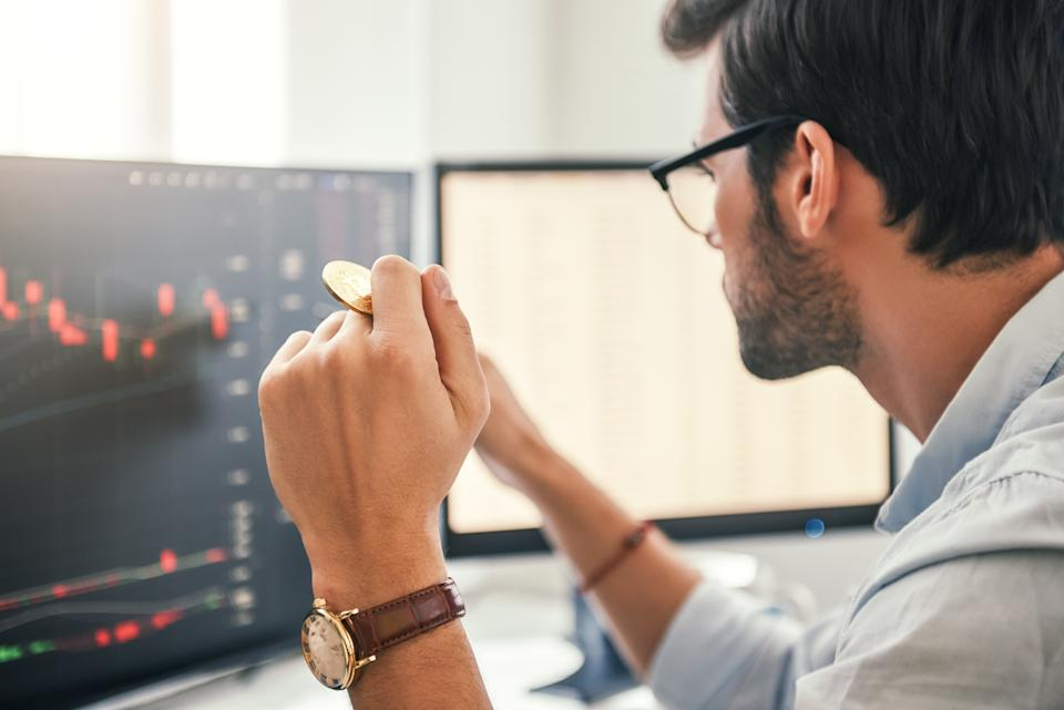 Investing. Close-up of young bearded trader in eyeglasses working with graph and financial reports on computer screen and holding Bitcoin in one hand while working his modern office. Crypto-currency. Virtual currency. Investment concept