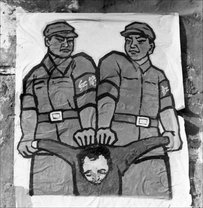 """A poster is displayed in late 1966 in a street in Beijing showing how to deal with so-called """"enemies of the people"""" during the Great Proletarian Cultural Revolution (AFP Photo/Jean Vincent)"""
