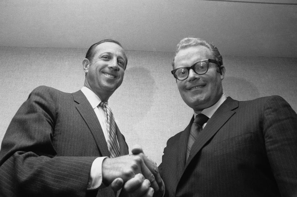 FILE - In this May 1969 file photo, NFL Commissioner Pete Rozelle, left, and Roone Arledge, president of ABC Sports, shake hands in New York, where it was announced that ABC would televise 13 regular-season games on Monday nights. Pete Rozelle would not be surprised to see the NFL's impact of television as it celebrates its 100th season this year. It was Rozelle, the commissioner from 1960 to 1989, who was able to convince owners that it was in their best interest to sign a leaguewide rights deal instead of teams negotiating on their own. (AP Photo/File)