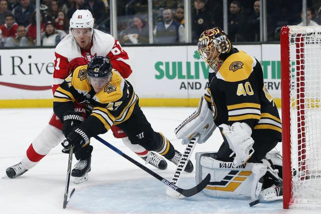 Detroit Red Wings' Jacob de la Rose (61) and Boston Bruins' Torey Krug (47) battle for the puck in front of Bruins goaltender Tuukka Rask (40) during the third period of an NHL hockey game in Boston, Saturday, Dec. 1, 2018. (AP Photo/Michael Dwyer)