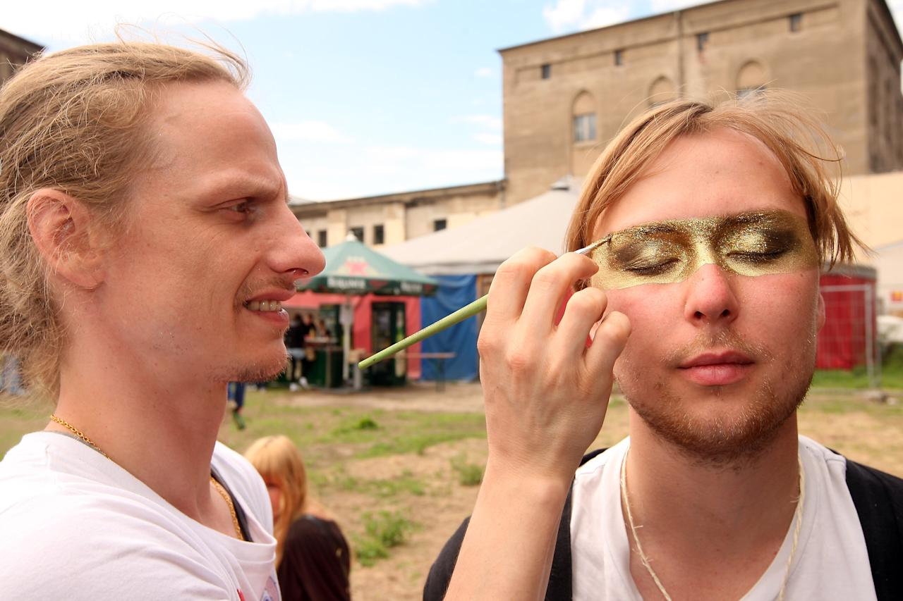 "BERLIN, GERMANY - JULY 21:  An attendee gets his face painted with glitter at the second annual Hipster Olympics on July 21, 2012 in Berlin, Germany. With events such as the ""Horn-Rimmed Glasses Throw,"" ""Skinny Jeans Tug-O-War,"" ""Vinyl Record Spinning Contest"" and ""Cloth Tote Sack Race,"" the Hipster Olympics both mocks and celebrates the Hipster subculture, which some critics claim could never be accurately defined and others that it never existed in the first place. The imprecise nature of determining what makes one a member means that the symptomatic elements of adherants to the group vary in each country, but the archetype of the version in Berlin, one of the more popular locations for those following its lifestyle, along with London and Brooklyn, includes a penchant for canvas tote bags, the carbonated yerba mate drink Club Mate, analogue film cameras, an asymetrical haircut, 80s neon fashion, and, allegedly, a heavy dose of irony. To some in Berlin, members of the hipster ""movement"" have replaced a former unwanted identity in gentrifying neighborhoods, the Yuppie, for targets of criticism, as landlords raise rents in the areas to which they relocate, particularly the up-and-coming neighborhood of Neukoelln.  (Photo by Adam Berry/Getty Images)"