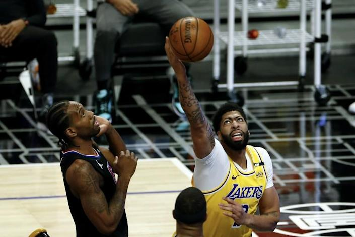 Los Angeles Lakers' Anthony Davis, right, goes up to basket next to Los Angeles Clippers' Kawhi Leonard, left, during the first half of an NBA basketball game, Thursday, May 6, 2021, in Los Angeles. (AP Photo/Ringo H.W. Chiu)