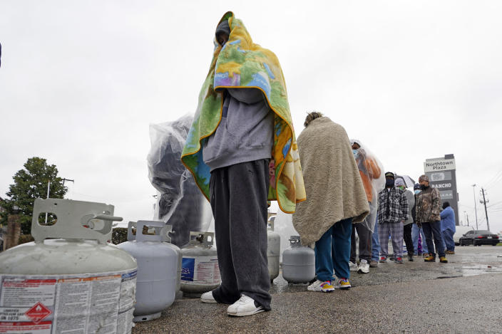 Carlos Mandez waits in line to fill his propane tanks Wednesday, Feb. 17, 2021, in Houston. Customers had to wait over an hour in the freezing rain to fill their tanks. Millions in Texas still had no power after a historic snowfall and single-digit temperatures created a surge of demand for electricity to warm up homes unaccustomed to such extreme lows, buckling the state's power grid and causing widespread blackouts. (AP Photo/David J. Phillip)