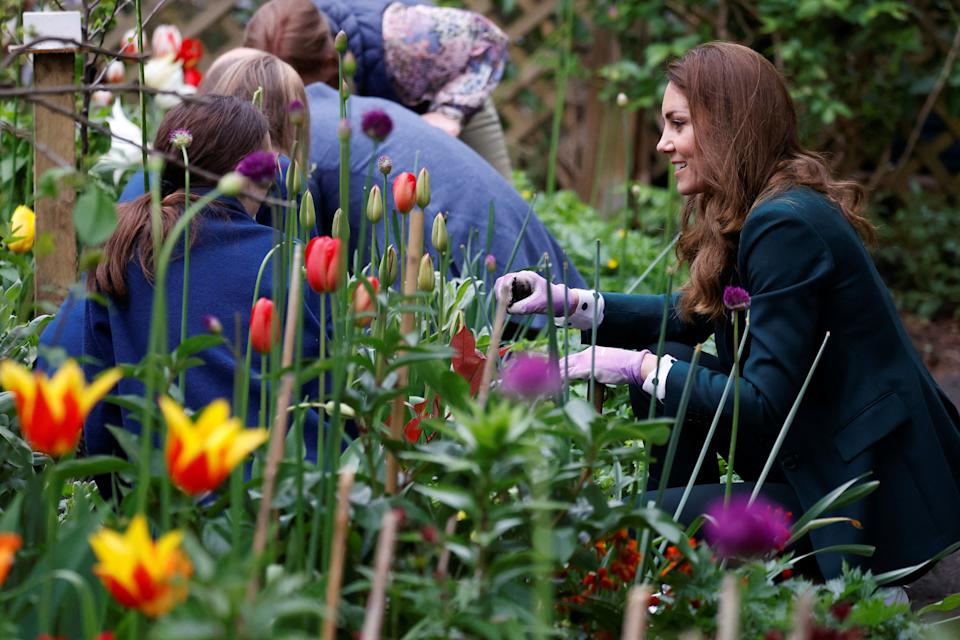 Britain's Catherine, Duchess of Cambridge plants sunflower seeds with volunteers as she visits Starbank Park to hear about the work of Fields in Trust, along with Britain's Prince William, Duke of Cambridge, in Edinburgh, Scotland on May 27, 2021. (Photo by PHIL NOBLE / POOL / AFP) (Photo by PHIL NOBLE/POOL/AFP via Getty Images)