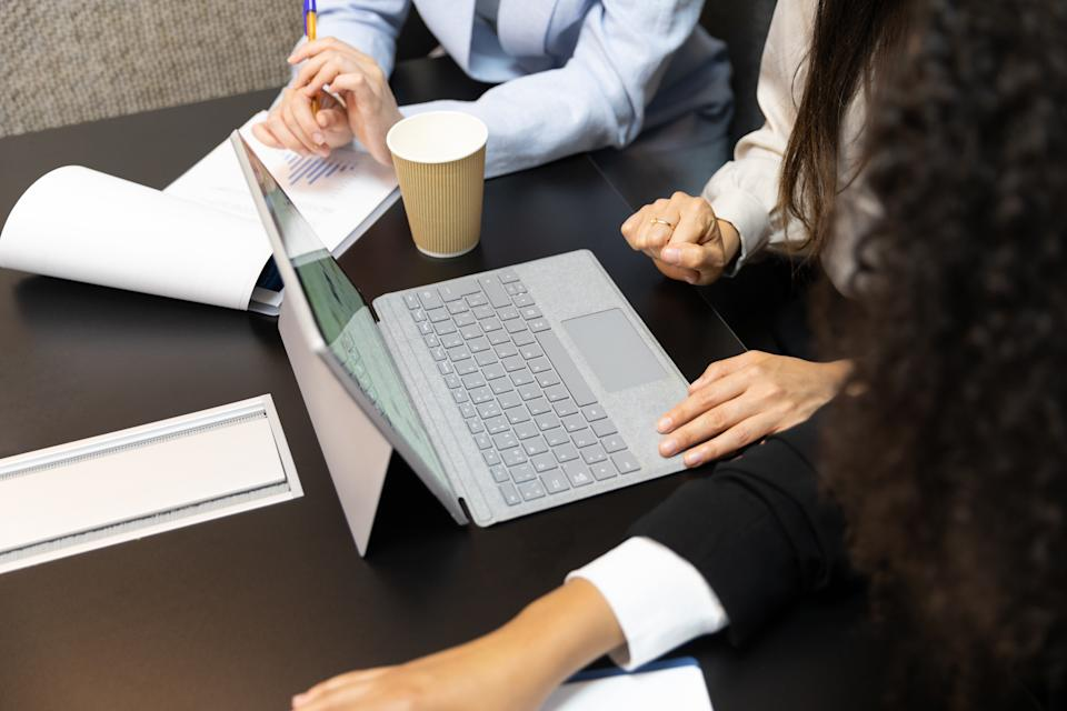 Unrecognized female office workers using digital tablet during a meeting.