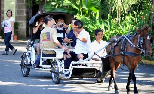 Tourists ride on a horse driven carriage in Intramuros in downtown Manila