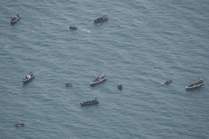 Rubber boats carrying divers position themselves as the search for the wreckage of a crashed Sriwijaya Air passenger jet continues, in this photo taken from an Indonesian Navy airplane over the Java Sea, off Jakarta, Indonesia, Tuesday, Jan. 12, 2021. Indonesian navy divers were searching through plane debris and seabed mud Tuesday looking for the black boxes of the Sriwijaya Air jet that nosedived into the Java Sea over the weekend with 62 people aboard. (AP Photo/Eric Ireng)