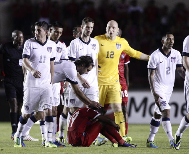 Graham Zusi of the U.S. reaches out to a dejected Alberto Quintero of Panama after the U.S. defeated Panama in a 2014 World Cup qualifying soccer match in Panama City, Tuesday, Oct. 15, 2013. The United States rallied for a 3-2 win at Panama on Tuesday night that left Mexico's World Cup hopes alive and knocked out the Panamanians. (AP Photo/Arnulfo Franco)