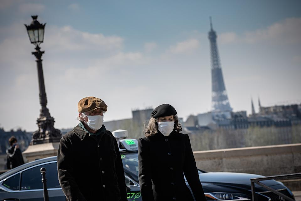 PARIS, March 20, 2021 -- People with face masks walk on a street in Paris, France, on March 20, 2021. French Prime Minister Jean Castex on Thursday announced