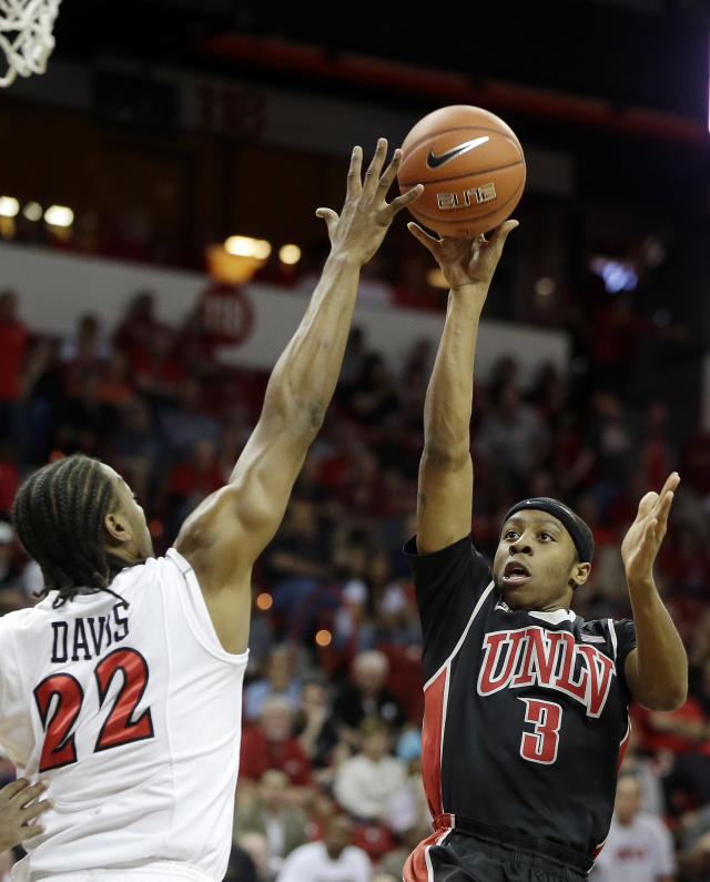 UNLV's Kevin Olekaibe shoots over San Diego State's Josh Davis during the first half of an NCAA college basketball game in the semifinals of the Mountain West Conference tournament Friday, March 14, 2014, in Las Vegas. (AP Photo/Isaac Brekken)