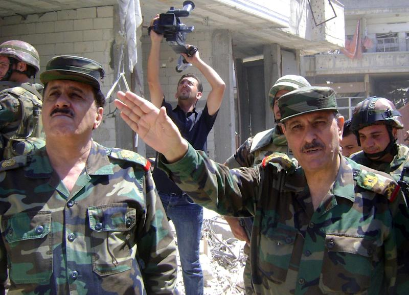 A picture released by the Syrian Arab News Agency on August 5, 2013 shows Defence Minister General Fahd al-Freij (R) talking to the media in Homs, Syria