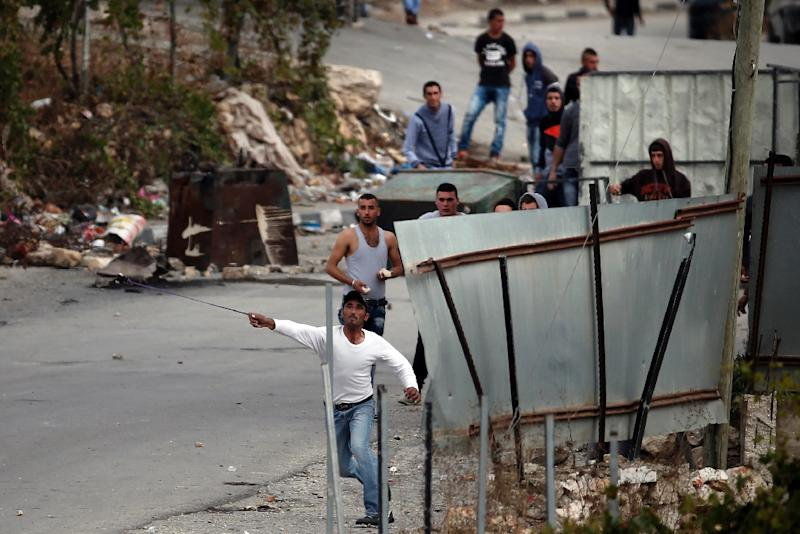Palestinian protesters in the West Bank village of Sair hurl rocks at Israeli soldiers in the Beit Einun junction east of Hebron on October 26, 2015 (AFP Photo/Thomas Coex)