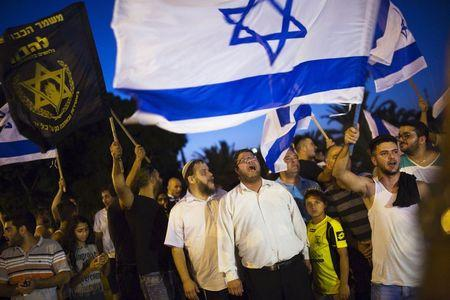 Right-wing activists hold Israeli national flags, during a protest in support of a hunger-striking Palestinian prisoner, Mohammed Allan, in the southern city of Ashkelon August 16, 2015. REUTERS/Amir Cohen