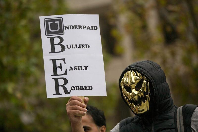 An Uber driver wearing a mask holds up a sign during a protest against a rise in the commission (Bloomberg)