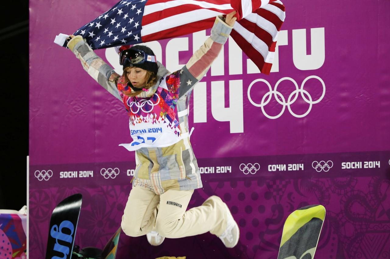Winner Kaitlyn Farrington of the U.S. celebrates with the U.S. flag after the women's snowboard halfpipe finals at the 2014 Sochi Winter Olympic Games in Rosa Khutor February 12, 2014. REUTERS/Mike Blake (RUSSIA - Tags: OLYMPICS SPORT SNOWBOARDING TPX IMAGES OF THE DAY)