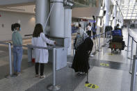 Healthcare workers check the temperature of passengers at the departure terminal of the Rafik Hariri International Airport in Beirut, Lebanon, Wednesday, July 1, 2020. Beirut's airport is partially reopening after a three-month shutdown and Lebanon's cash-strapped government is hoping that Thousands of Lebanese expatriates will return for the summer, injecting dollars into the country's sinking economy. (AP Photo/Bilal Hussein)