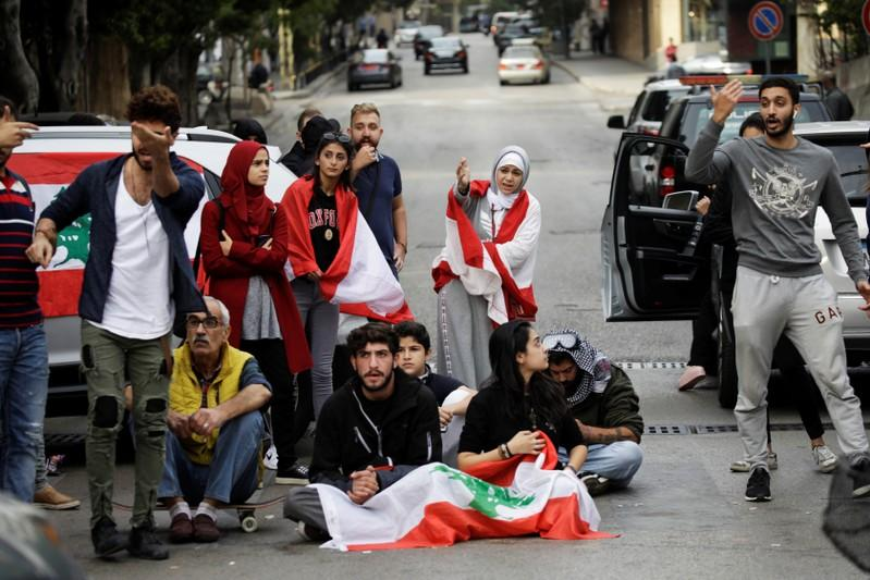 Protesters gesture towards a driver at a roadblock during ongoing anti-government demonstrations in Beirut