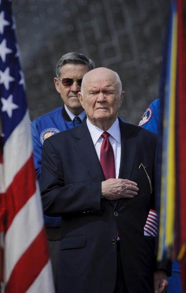 In this photo provided by NASA, ormer astronaut and U.S. Senator John Glenn holds his hand to his heart during the playing of the National Anthem at the transfer ceremony for space shuttle Discovery, Thursday, April 19, 2012, at the Smithsonian's Steven F. Udvar-Hazy Center in Chantilly, Va. Space shuttle Discovery will take the place of Enterprise at the center to commemorate past achievements in space and retire as an artifact representing the 30-year shuttle program. (AP Photo/NASA, Paul E. Alers) MANDATORY CREDIT