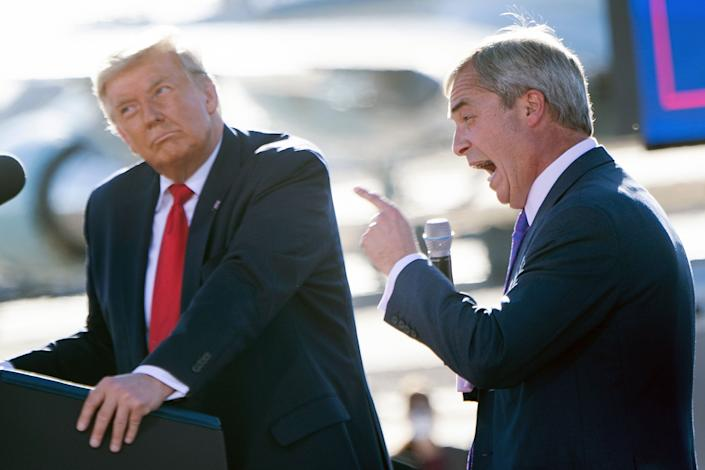 US President Donald Trump listens as Nigel Farage (R) speaks during a Make America Great Again rally at Phoenix Goodyear Airport October 28, 2020, in Goodyear, Arizona. (Photo by Brendan Smialowski / AFP) (Photo by BRENDAN SMIALOWSKI/AFP via Getty Images)