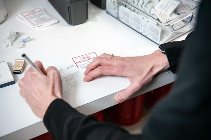 Pharmacist Brittany Marsh fills out a COVID-19 vaccine card for a patient at her pharmacy in Little Rock, Ark., on March 8, 2021. (Rory Doyle/The New York Times)