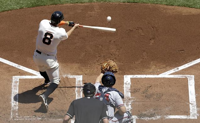 San Francisco Giants' Hunter Pence (8) hits a two-run home run off of Atlanta Braves pitcher Julio Teheran in front of catcher Evan Gattis during the first inning of a baseball game in San Francisco, Wednesday, May 14, 2014. (AP Photo)