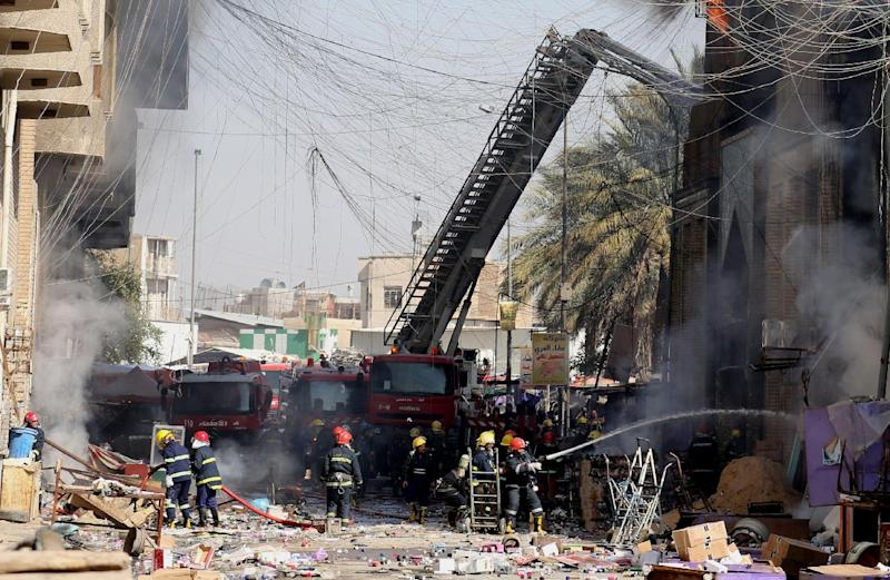 Iraqi firefighters try to extinguish fire after two bombs went off in Baghdad, Iraq, Thursday, Feb. 13, 2014. A police officer says two bombs, hidden in clothing stalls in the capital's al-Arabi wholesale market, went off simultaneously on Thursday morning, wounding civilians. (AP Photo/Karim Kadim)