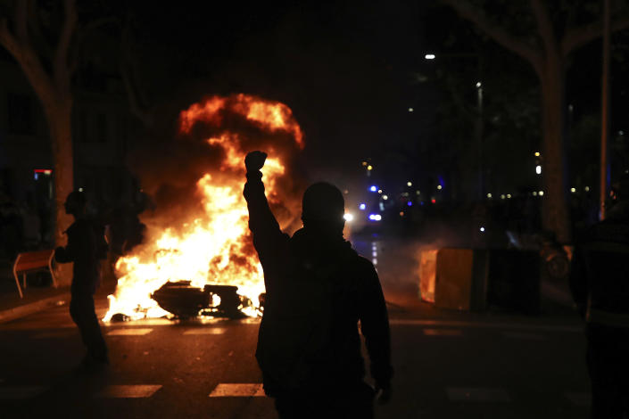 A protestors raises his fist at police across a burning barricade during clashes between protestors and police in Barcelona, Spain, Tuesday, Oct. 15, 2019. (Photo: Emilio Morenatti/AP)